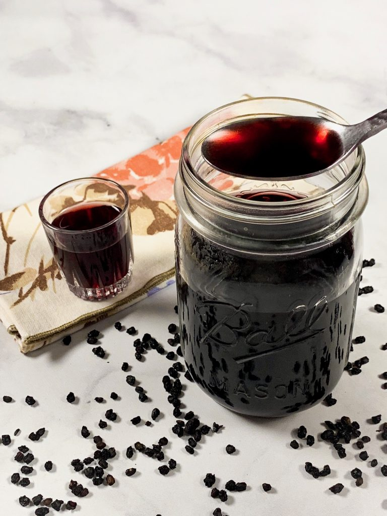 spoon holding vegan elderberry syrup recipe