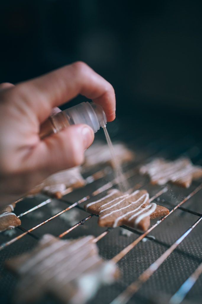 spraying flavor on salted caramel cookies with white chocolate drizzle