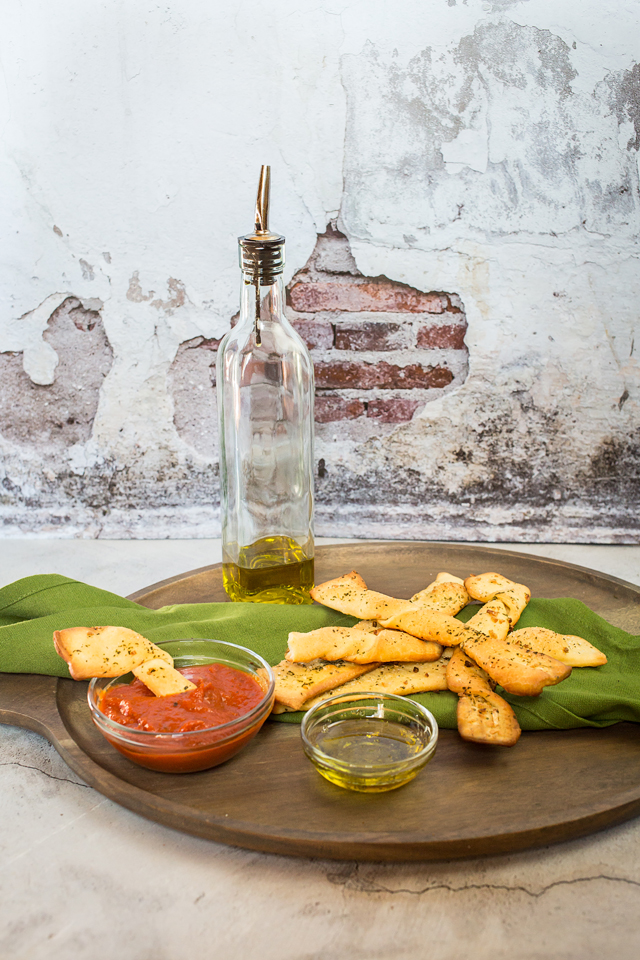 vegan breadsticks on plate with oil and dipping sauces