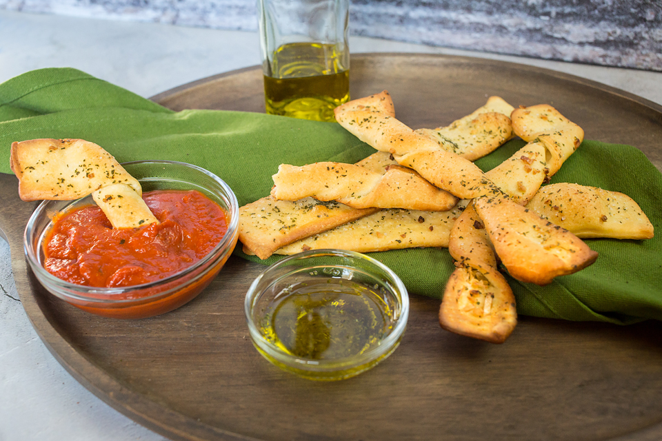 close up on a vegan garlic breadstick being dipped into sauce