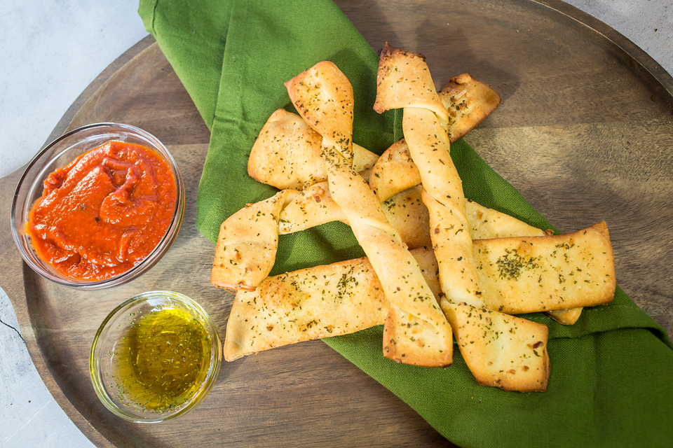 Photo of vegan breadsticks with dipping sauce.