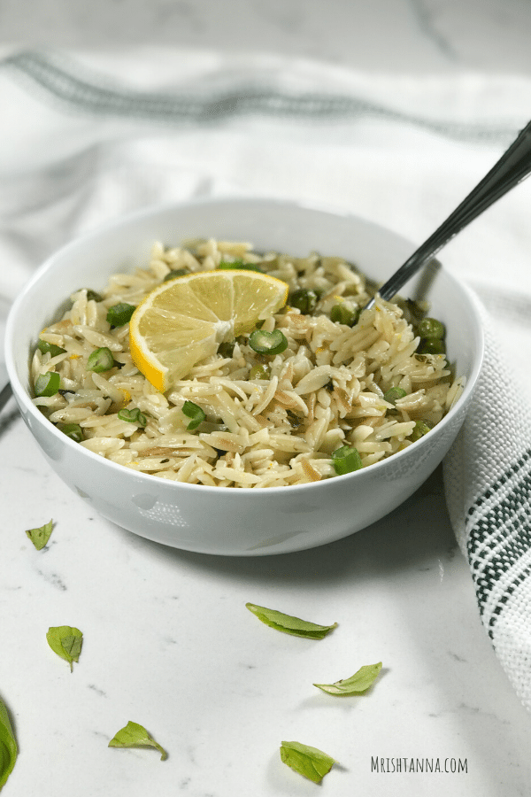 Photo of a white bowl with lemon orzo inside topped with a lemon wedge.