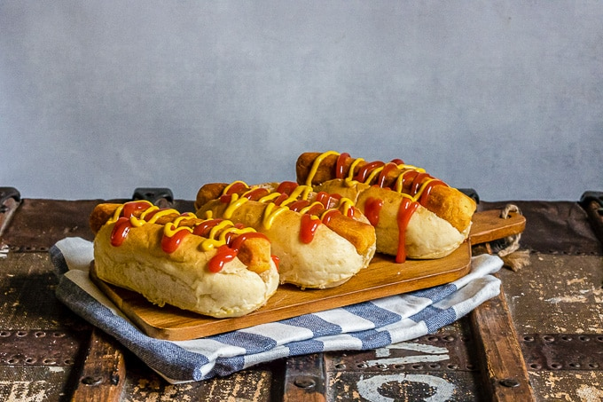 Photo of three vegan hot dogs in buns on a wooden serving board. The board in resting on a blue and white cloth on a rustic trunk.