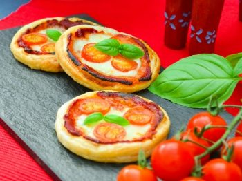 Photo of Mini Margherita Puff Pizza Pies. 3 mini margherita pizzas are seen on a slate board with a red table cloth underneath. Vine tomatoes and a bright green basil leaf is on the right of the image.