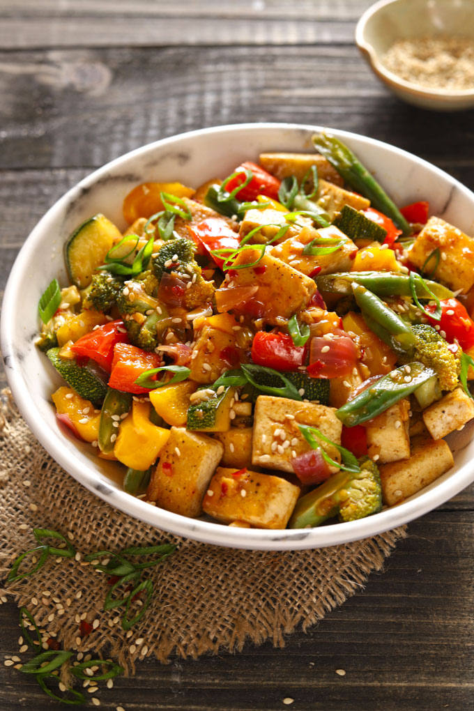 Photo of vegan tofu stir fry. Features a marble bowl with colorful vegetable stir fry with chunks of tofu on a wooden table.