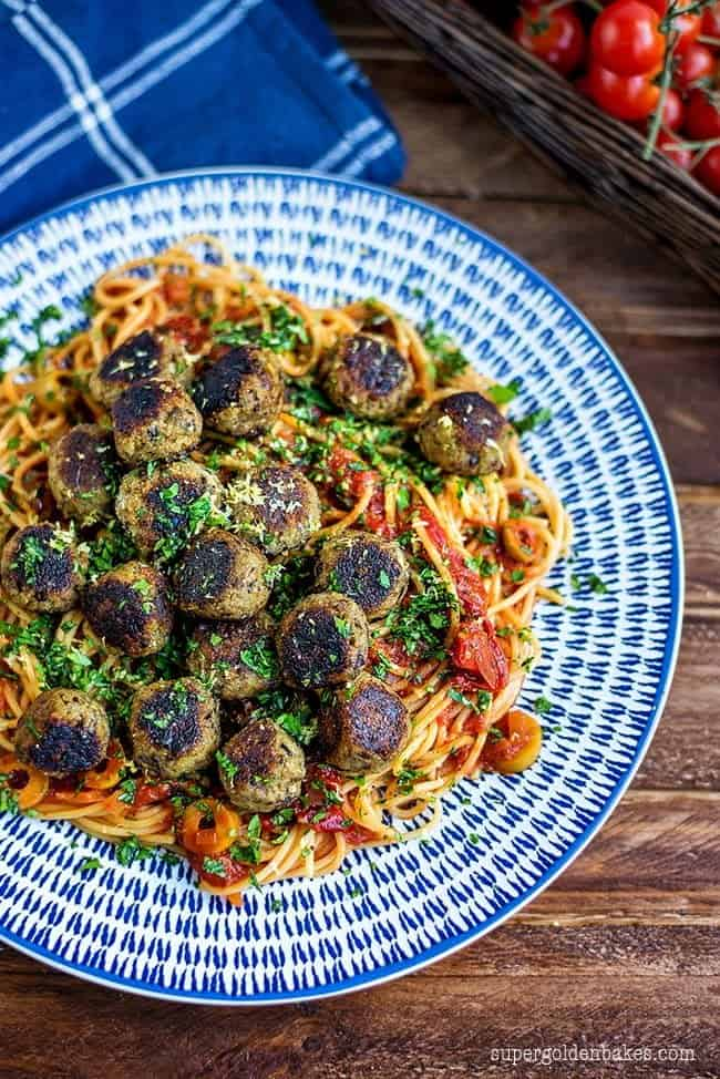 "Photo of vegan aubergine ""meatballs"". A blue and white plate is serving the dish. There is a basket of vine tomatoes and a blue with white stripes cloth napkin in the background."