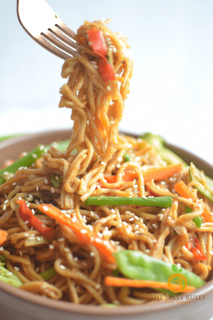 Photo of vegetable chow mein. A fork is seen with noodles dangling into the bowl. Some vegetables are seen as well as sesame seeds.