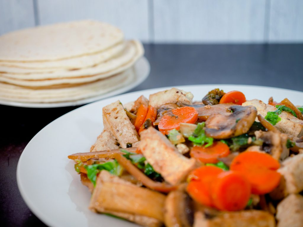 close up of moo shu vegetables with chinese pancakes in the background
