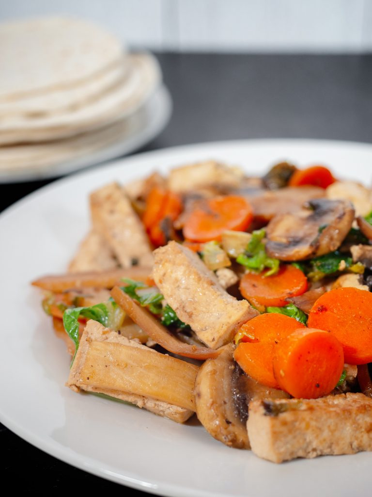 vertical shot of moo shu vegetables with chinese pancakes on black countertop
