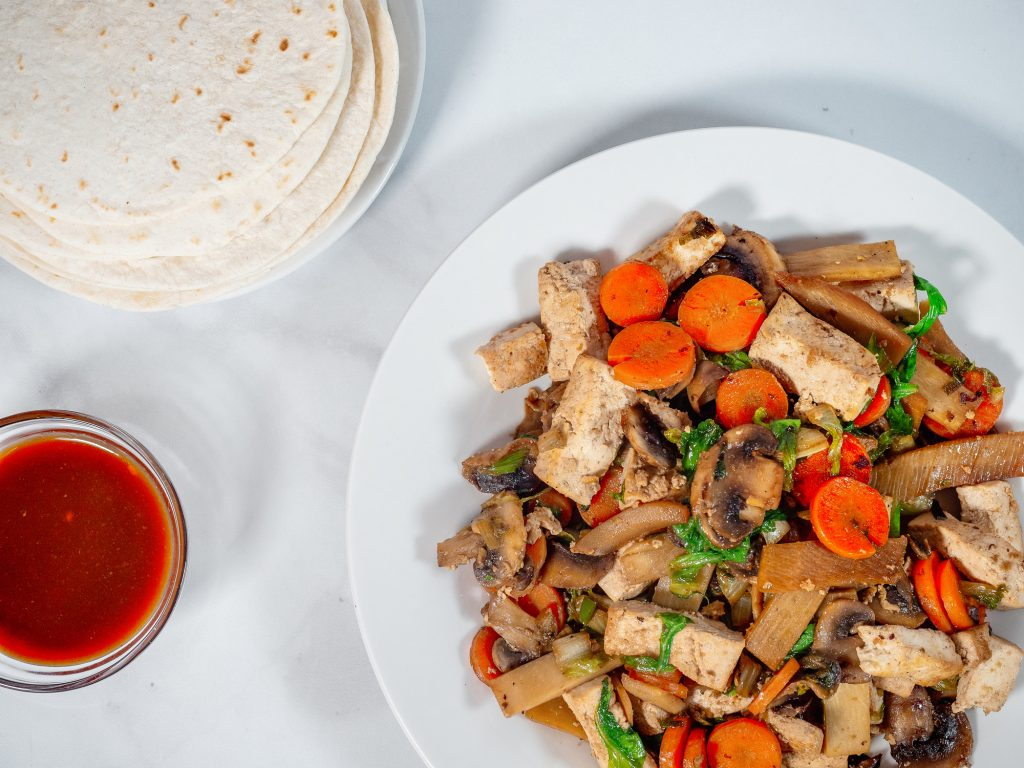 moo shu vegetables with chinese pancakes and hoisin sauce on white plate