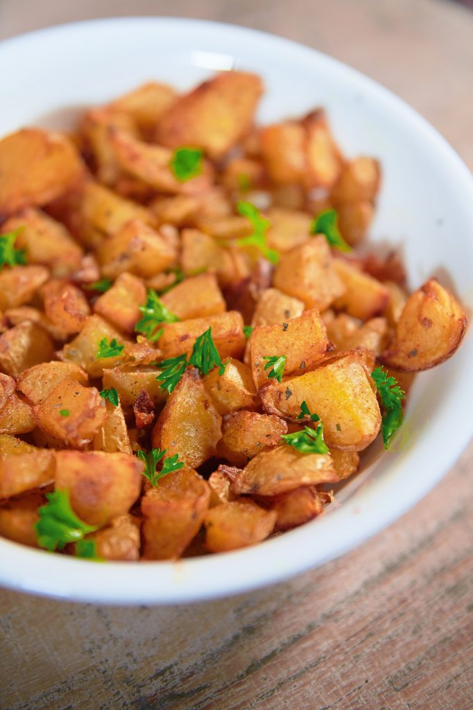 Photo of vegan roast potatoes in a white round bowl.