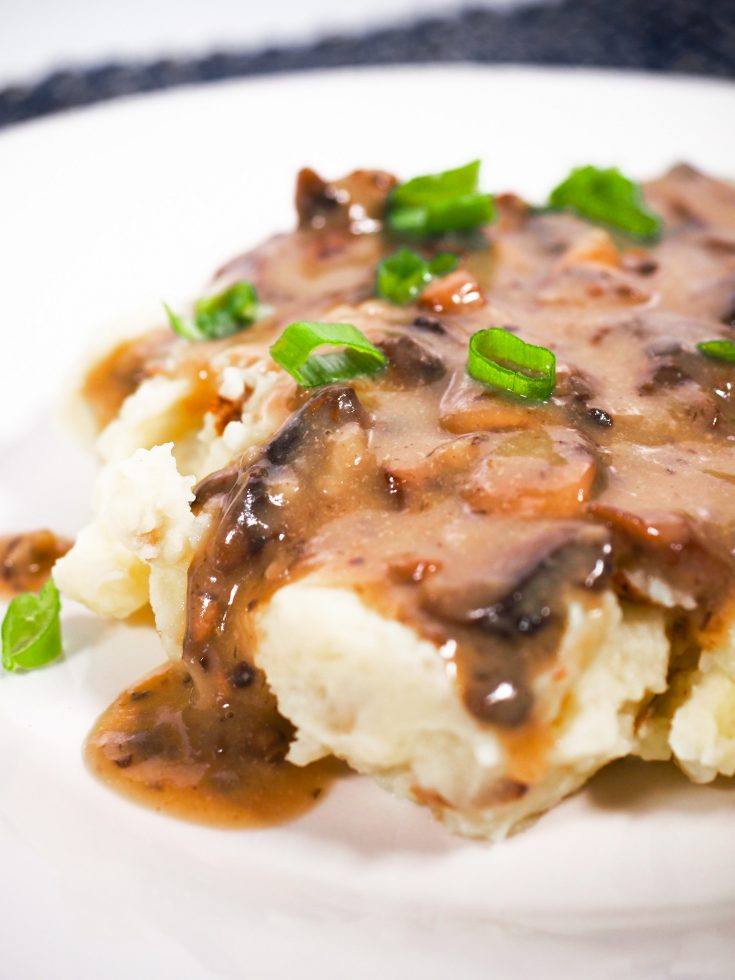close up of vegan gravy with mushrooms over mashed potatoes