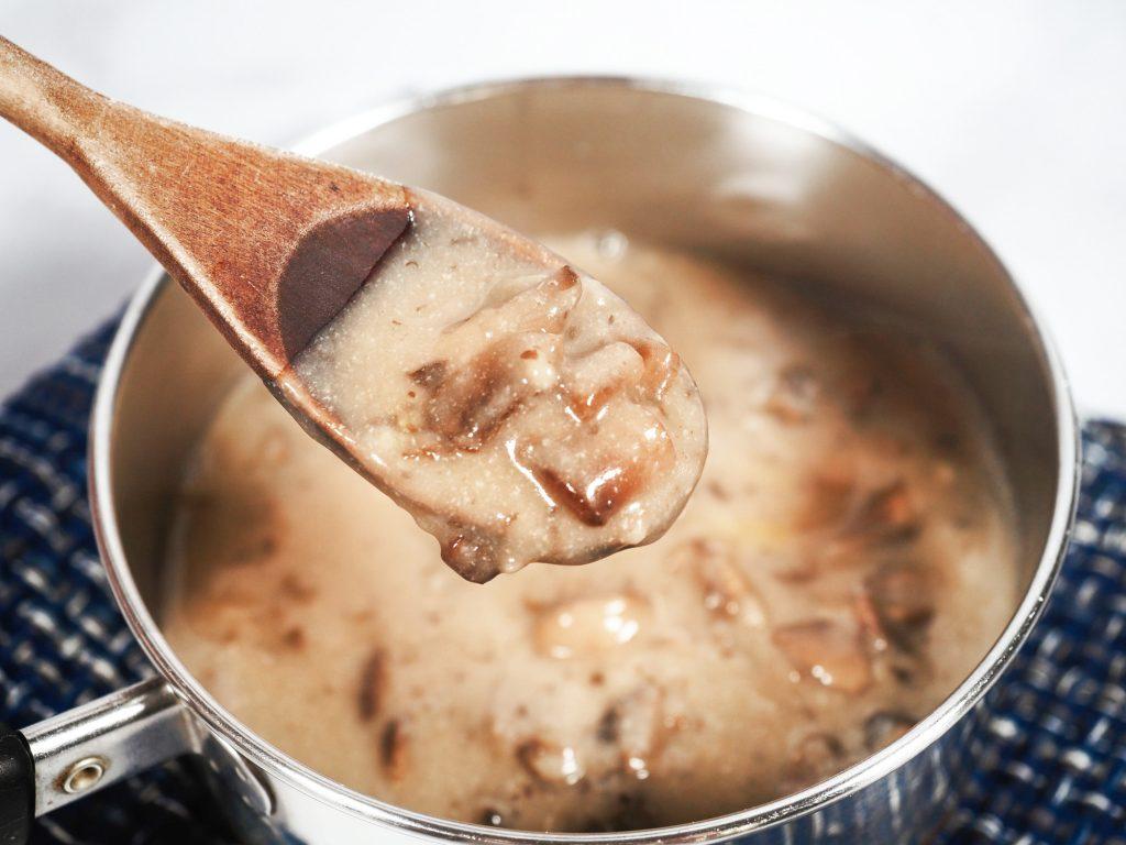 chopped mushrooms in pot of vegan brown gravy