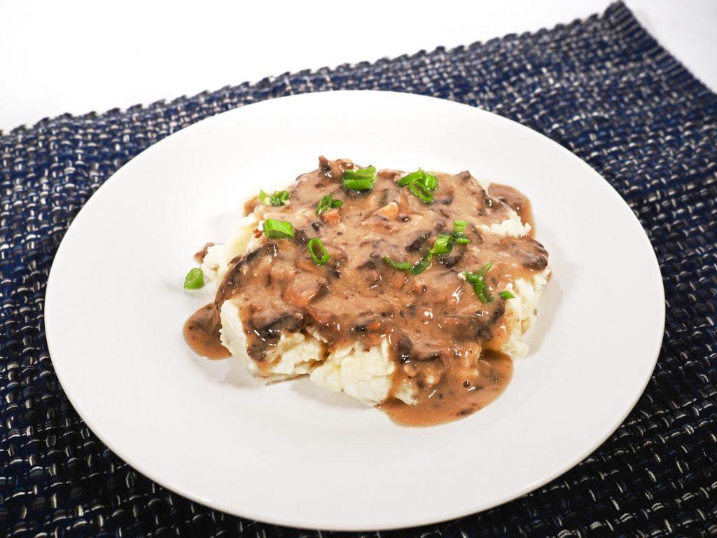 brown vegan gravy with mushrooms on mashed potatoes
