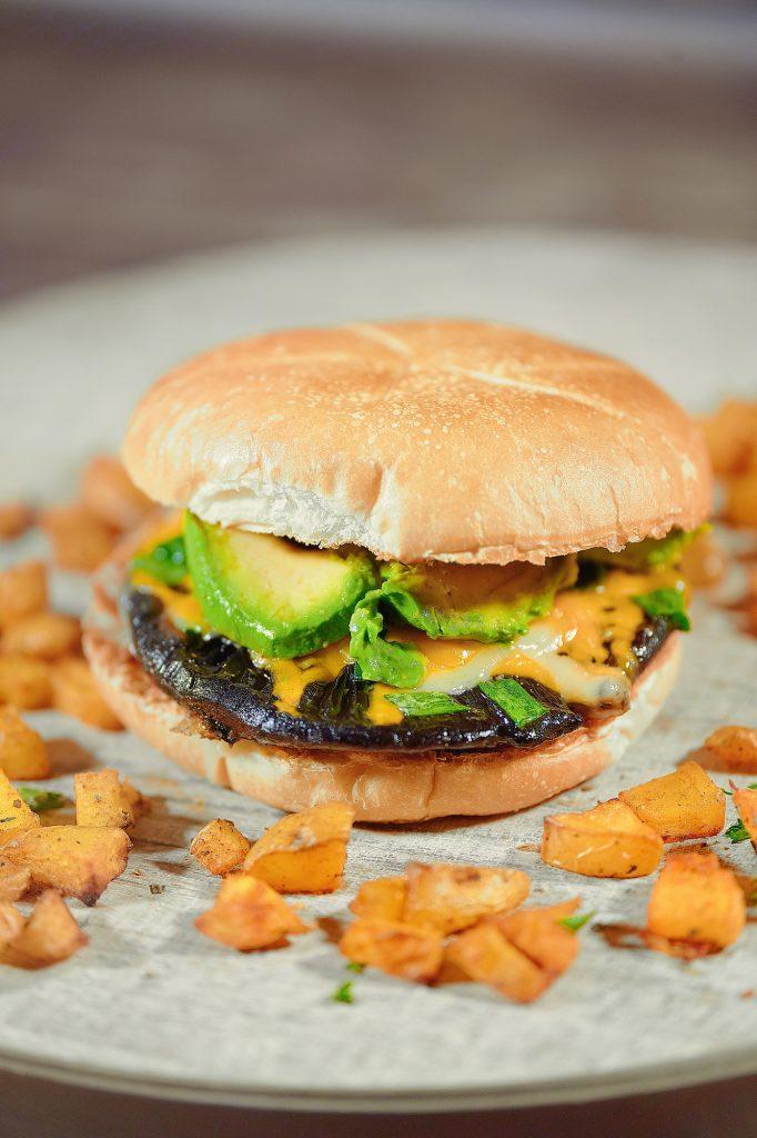 close up of vegan portobello mushroom burger with avocado