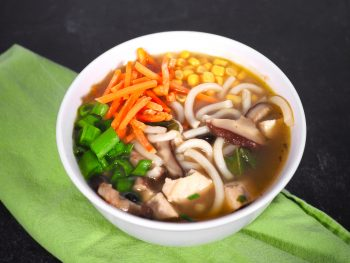 easy vegan udon noodle soup on black counter with green napkin