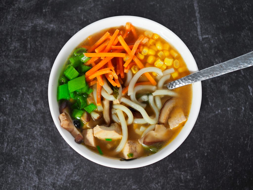 udon noodles in vegan broth on black countertop
