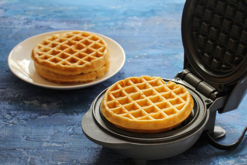 circular waffle iron on blue counter
