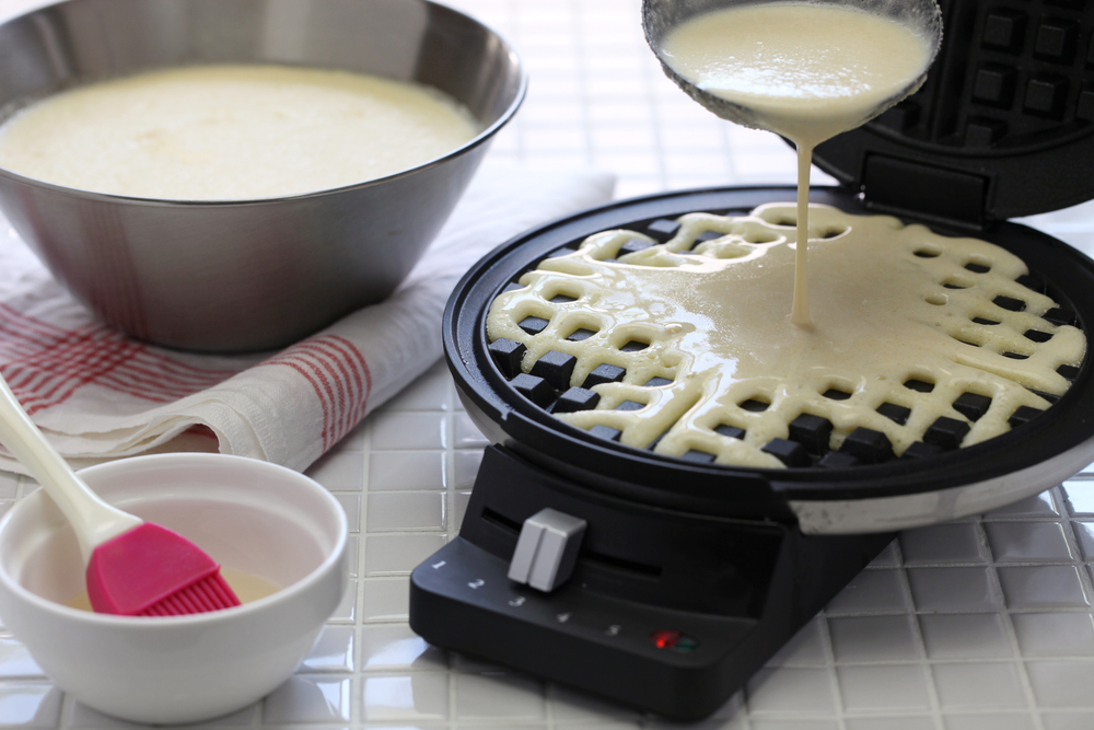 pouring batter on waffle maker with removable plates