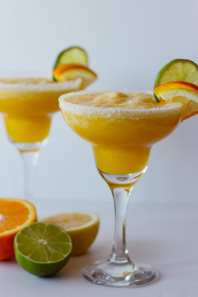 Photo of two fresh citrus margaritas with lemon, orange, and lime slices as a garnish.