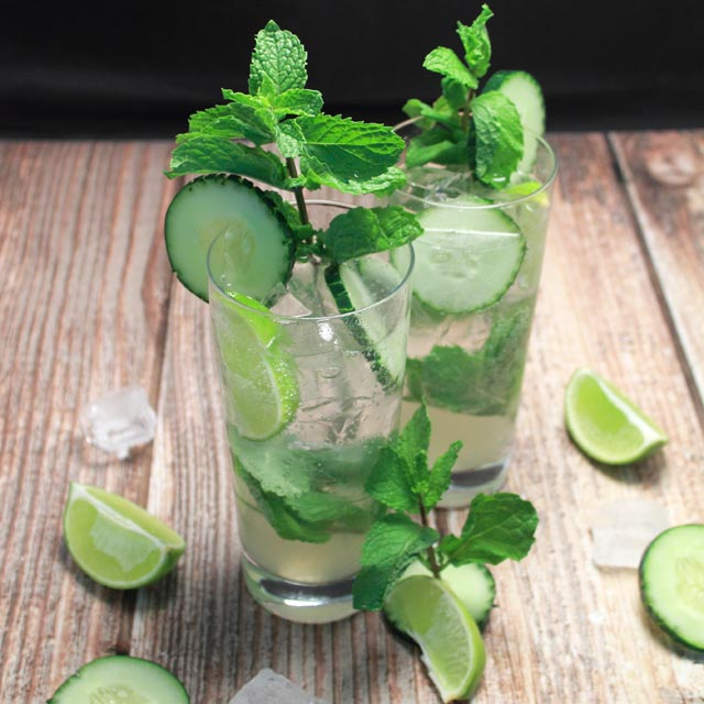 Photo of two light and fresh cucumber mojitos with cumcumber slices and mint sprigs as a garnish.