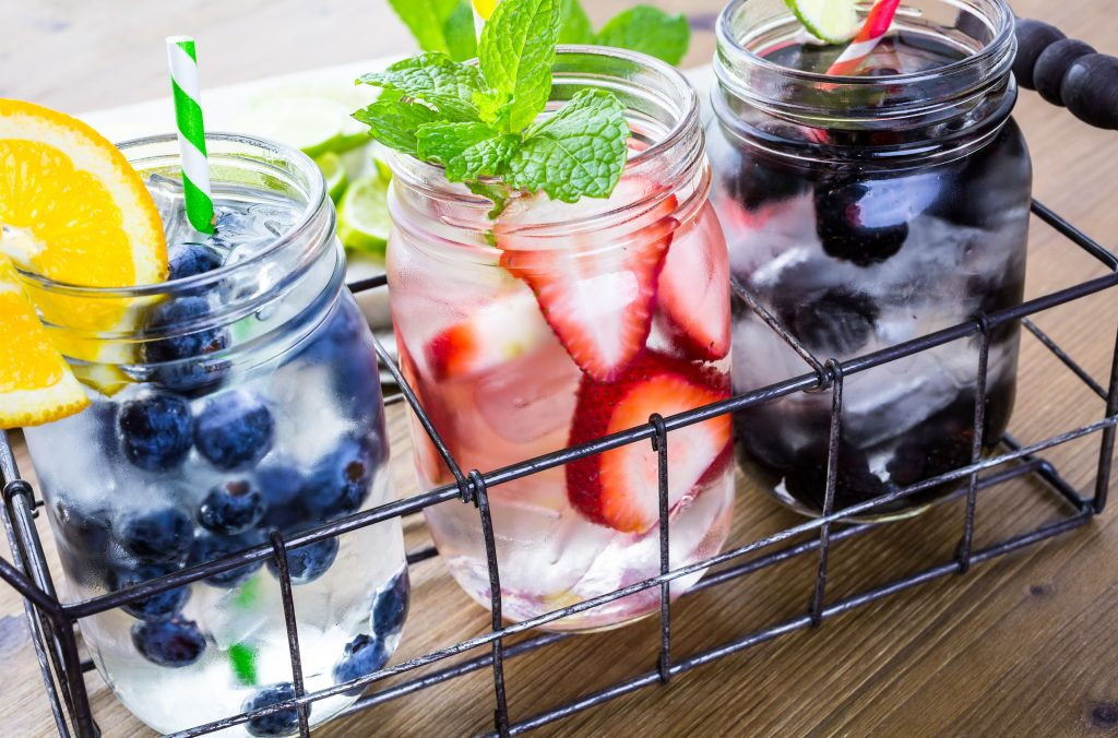 Photo of three fruity easy cocktails to make at home being served in mason jars all with fruit as a garnish.
