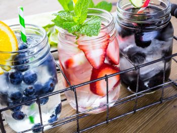 Photo of 3 fruity cocktails being served in glass mason jars.