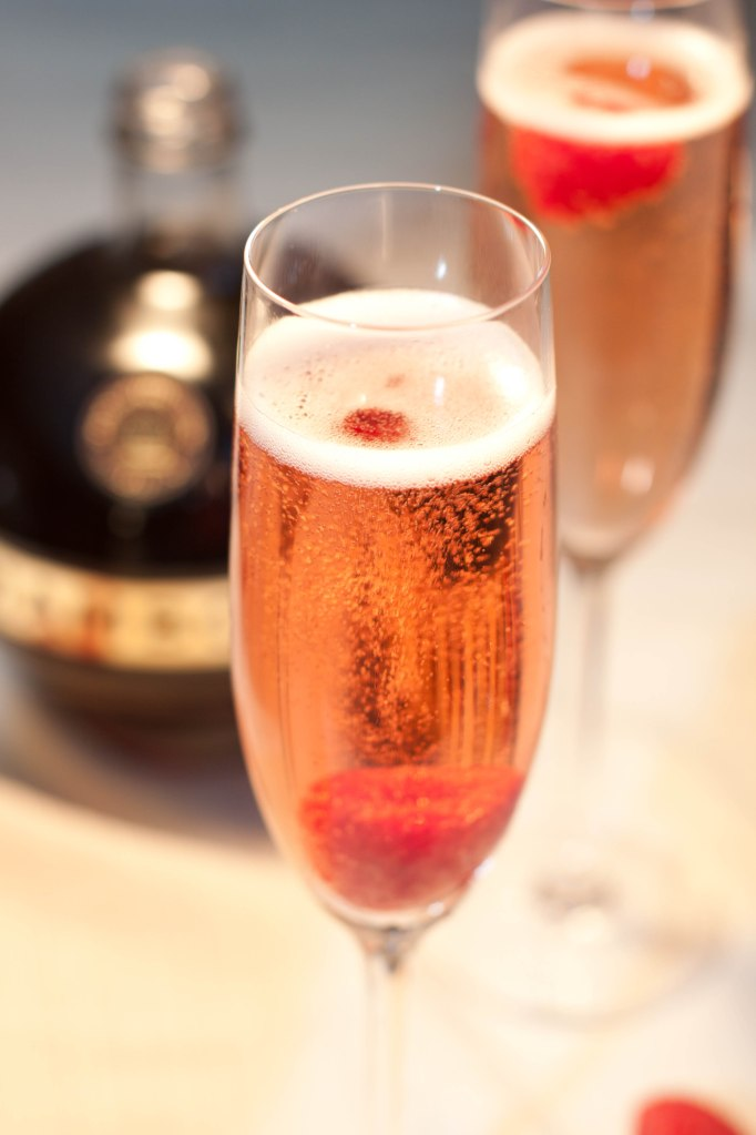 Photo of a champagne flute serving a french kiss cocktail with a raspberry garnish.