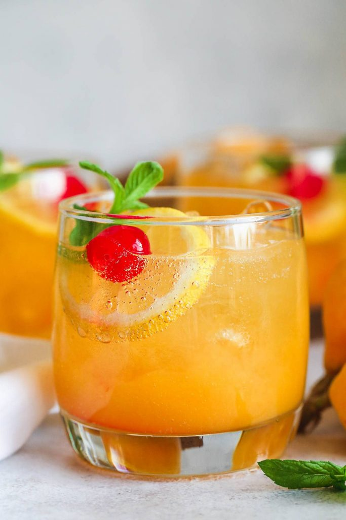 Photo of a loquat vodka cocktail with an orange slice and cherry garnish.