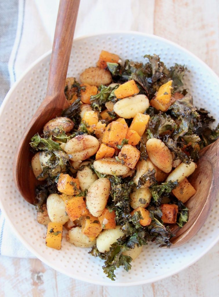 Photo of baked gnocchi with butternut squash and crispy kale being served in a white bowl with a textured rim with a wooden spoon.