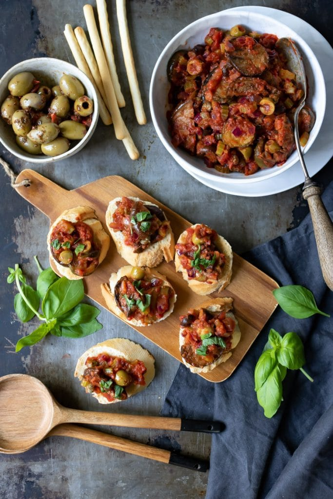 Photo of a wooden board serving caponata alla siciliana on crostinis next to a large bowl on the dish and a small bowl of olives.