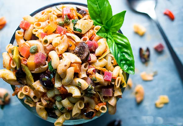 Photo a a small round plate overflowing with Italian vegan pasta salad. Of the vegan Italian recipes, this one will be a picnic favorite.
