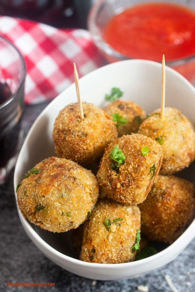 Photo of a deep bowl serving Neapolitan eggplant meatballs with toothpicks. A small bowl of red sauce is seen in the background.
