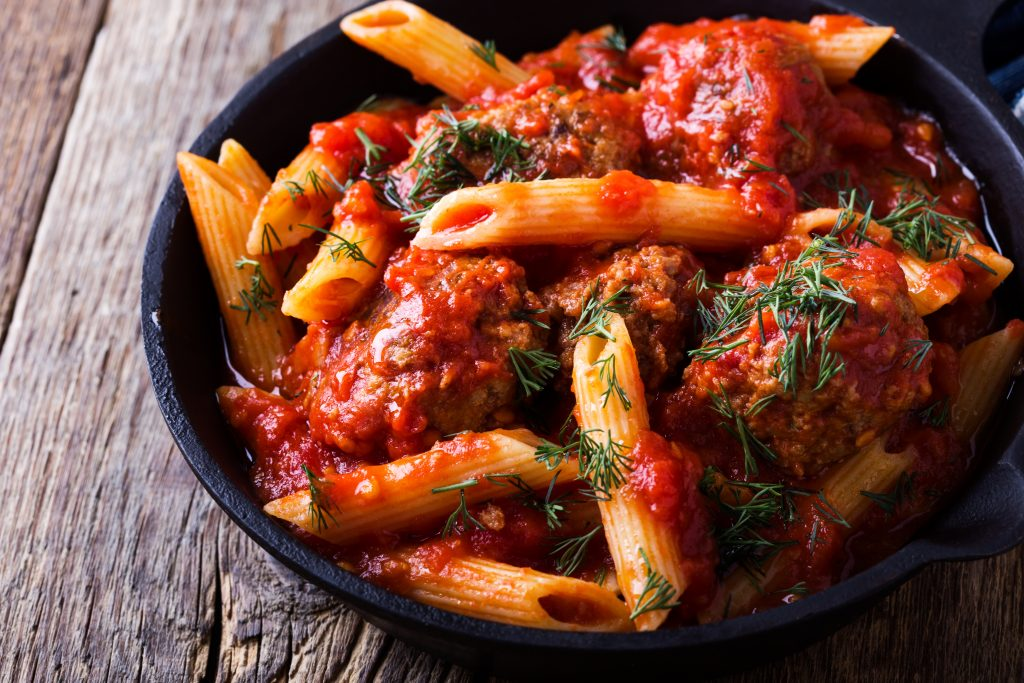 Photo of penne pasta with red sauce being served in a cast iron skillet.