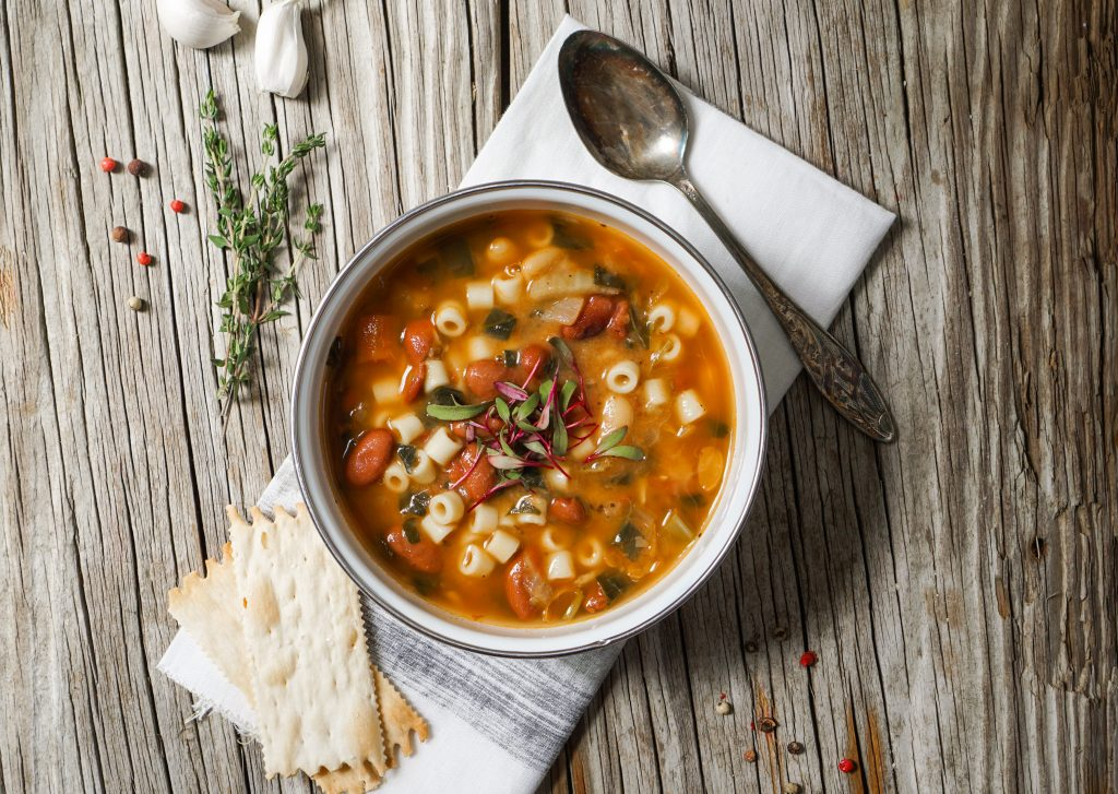 Photo of minestrone soup on a rustic wooden table with a cloth napkin.