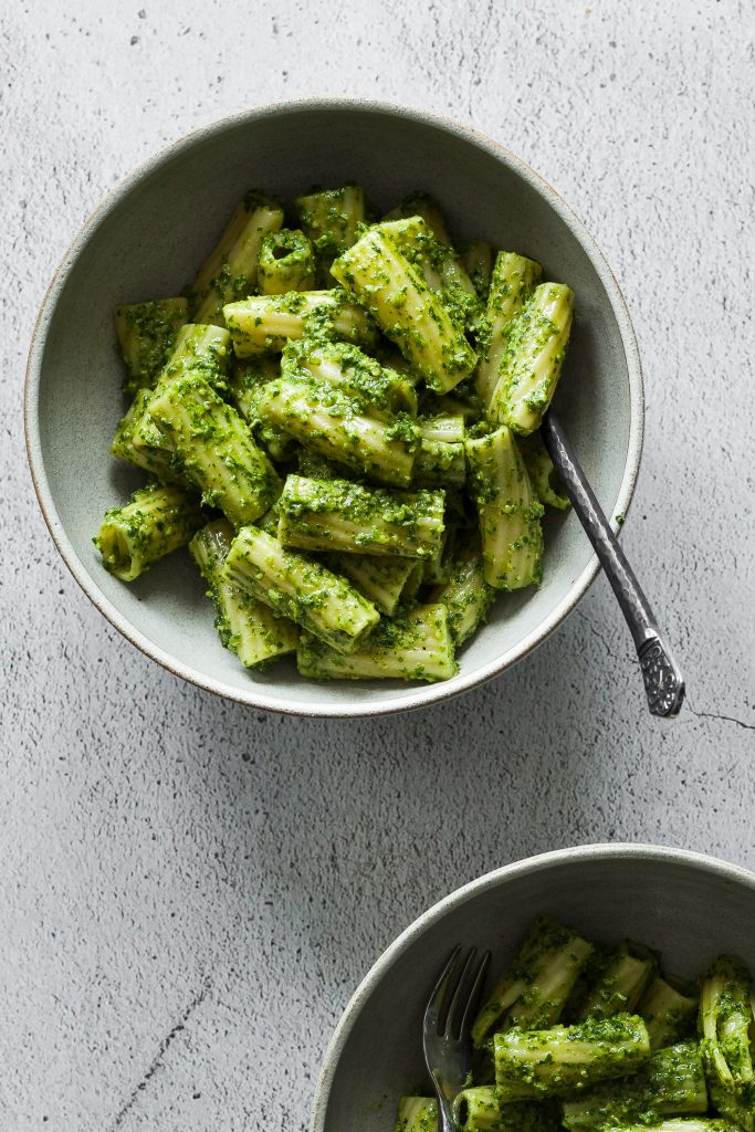 Photo of two bowls serving rigatoni with parsley walnut pesto.