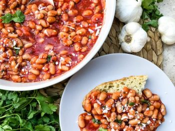 Photo of a large bowl serving arrabbiata beans one of the more spicy vegan Italian recipes.