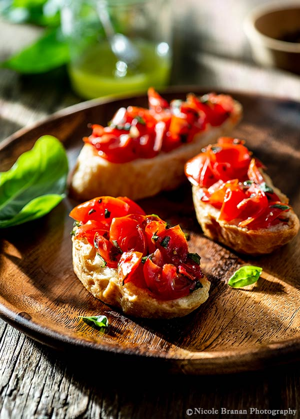 Photo of three baugette slices topped with bruschetta with basil-infused olive oil being served on a round wooden plate.
