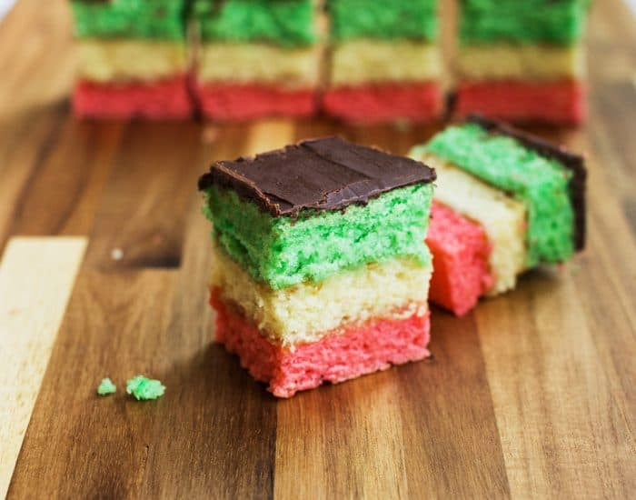 Photo of Italian Rainbow cookies which are colorful and resemble the Italian flag when cut into pieces. A real show stopper among the vegan Italian recipes.