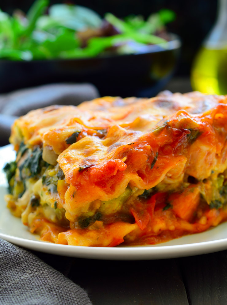 Photo of vegan lasagna being served on a white plate with a garden salad in the background. This is a stand out classic among the vegan Italian recipes.
