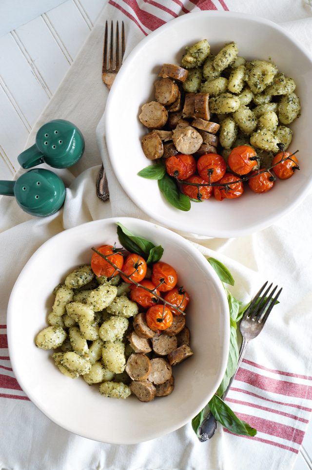 Photo of two white round bowls serving gnocchi with pesto, roasted tomatoes, and vegan sausage. This recipe proves that vegan Italian recipes can look complex and still be easy.