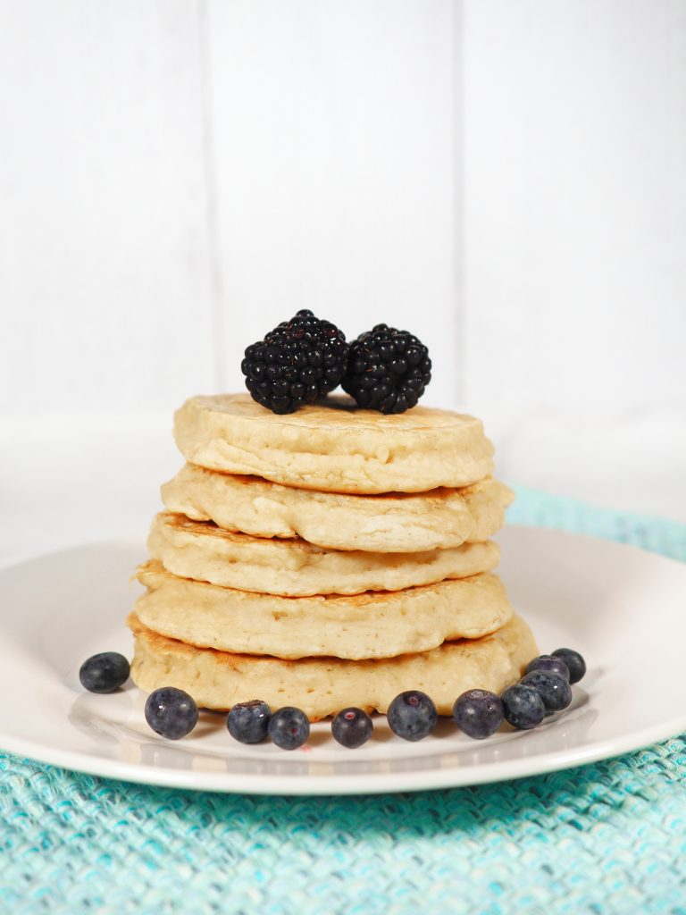 Photo of 5-ingredient vegan banana pancakes being served on a round white plate that is sitting upon an aqua woven place mat.  There are 5 pancakes stacked on top of each other with blueberries and blackberries.