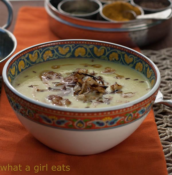 Photo of a small bowl with a colorfully decorated rim serving curried cauliflower soup.