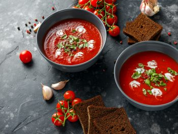 Photo of two bowls serving creamy tomato basil soup.