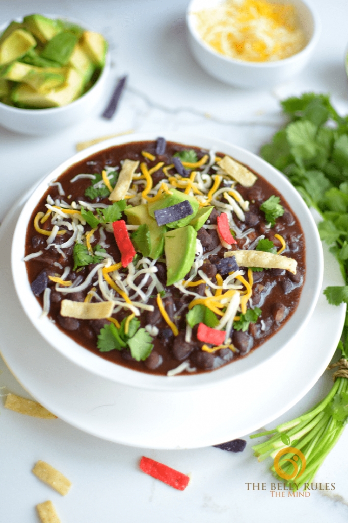 Photo of spicy black bean soup being served in a round white bowl with avocado, cheese, and tortilla strips as a garnish.