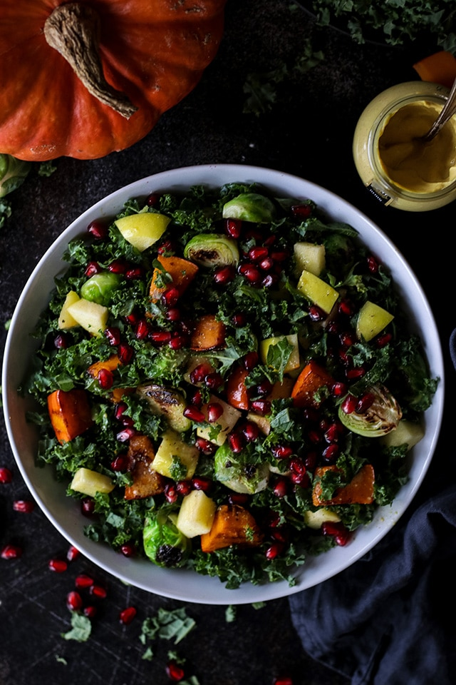 Photo of vegan fall harvest salad with kale and pumpkin being served in a large round white bowl.