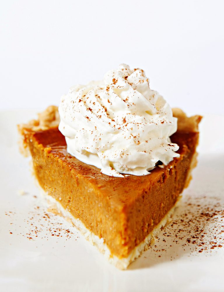 Photo of a slice of vegan thanksgiving pumpkin pie topped with whipped cream and cinnamon.