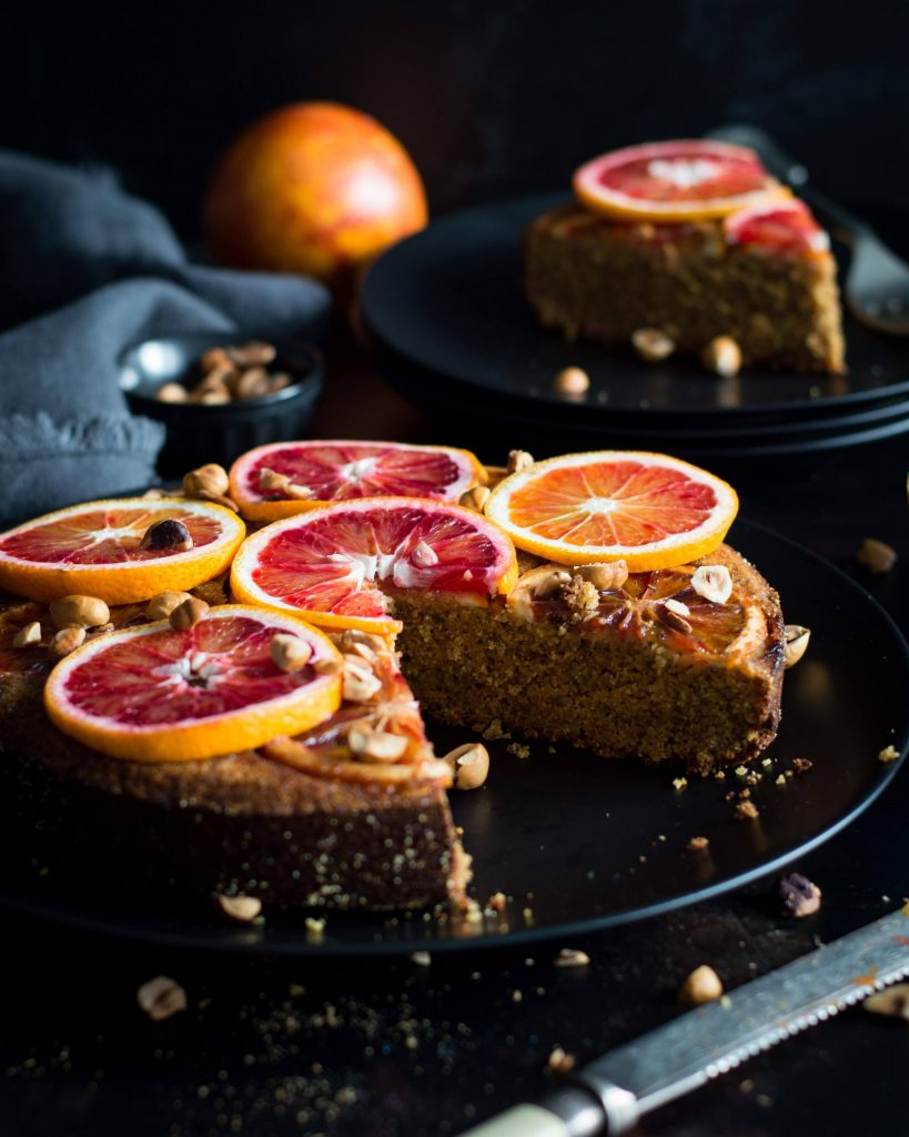 Photo of upside down blood orange cake being served on a dark round plate.