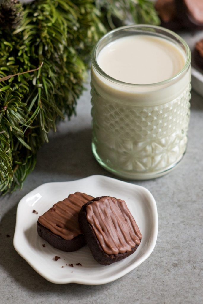 Photo of two vegan chocolate ginger cookies being served with a glass of milk.