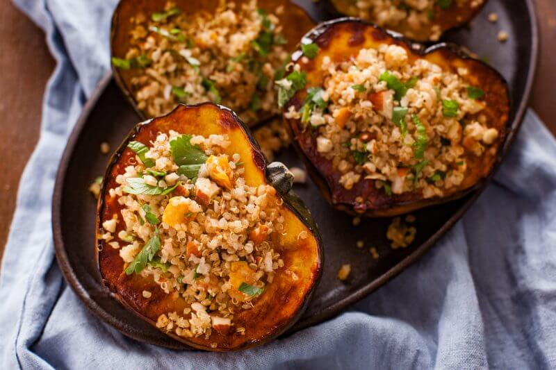 Photo of quinoa stuffed squash with almonds and apricots being served on an oval plate.